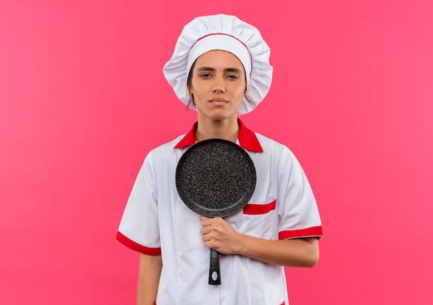 Vermoeide jonge vrouwelijke kok die de koekenpan van de chef-kok eenvormige holding met exemplaarruimte draagt