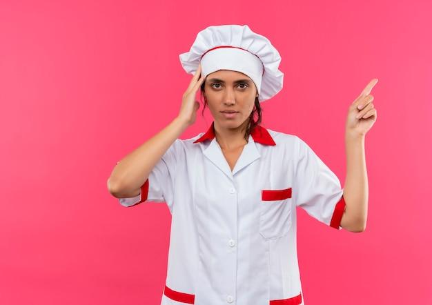 Vermoeide jonge vrouwelijke kok die eenvormige chef-kok draagt ?? wijst naar kant hand op hoofd met exemplaarruimte zetten