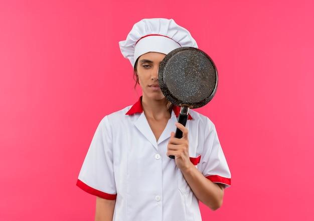 Vermoeide jonge vrouwelijke kok die koekenpan van het chef-kok uniform behandelde oog met exemplaarruimte draagt