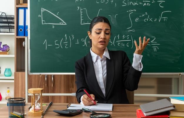 Vermoeide jonge vrouwelijke leraar zit aan tafel met schoolbenodigdheden die iets schrijven dat hand in de klas verspreidt