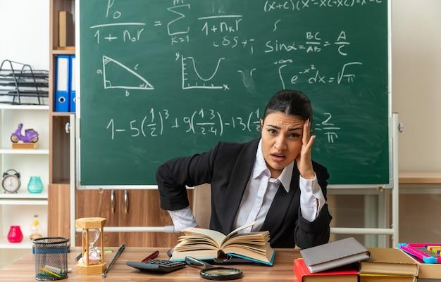 Vermoeide jonge vrouwelijke leraar zit aan tafel met schoolbenodigdheden en legt de hand op de wang in de klas