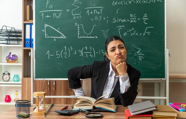 Vermoeide jonge vrouwelijke leraar zit aan tafel met schoolspullen en steekt vuist onder de kin in de klas