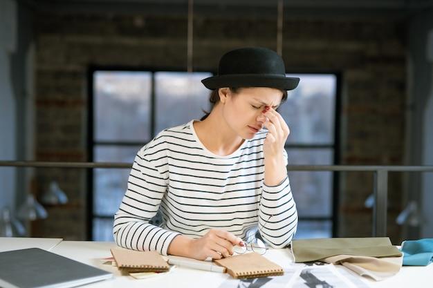 Vermoeide jonge vrouwelijke ontwerper in hoed en gestreepte pullover probeert zich te concentreren tijdens het werken aan nieuwe modeschetsen