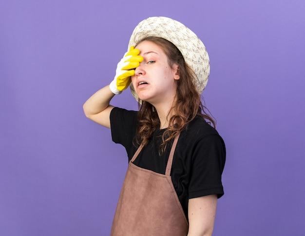 Vermoeide jonge vrouwelijke tuinman die tuinhoed draagt met handschoenen bedekt oog met hand