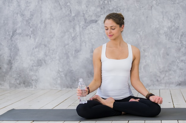 Vermoeide jonge vrouwen in sportkleding drinkwater zittend op de oefeningsmat