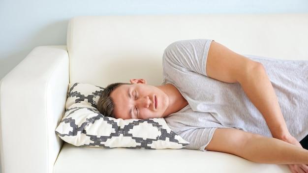 Vermoeide jongeman met gesloten ogen in wit t-shirt ligt op een zachte bank met een klein designkussen in een lichte kamer thuis close-up