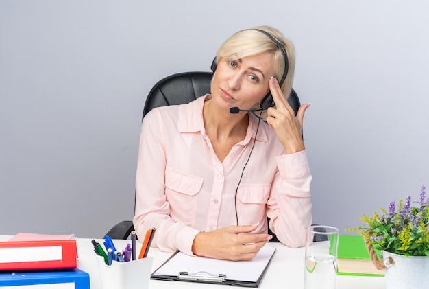 Vermoeide, kantelende hoofd jonge vrouwelijke callcenter-operator die een hoofdtelefoon draagt die aan tafel zit met kantoorhulpmiddelen die zelfmoordgebaar tonen dat op een witte muur wordt geïsoleerd