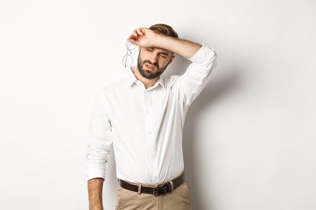 Vermoeide kantoormedewerker zet bril af, veegt het zweet van het voorhoofd af met zijn arm, staat leeg
