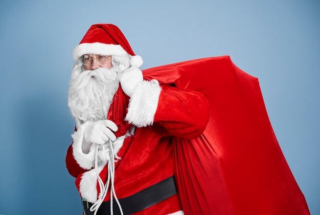Vermoeide kerstman die zware zak draagt