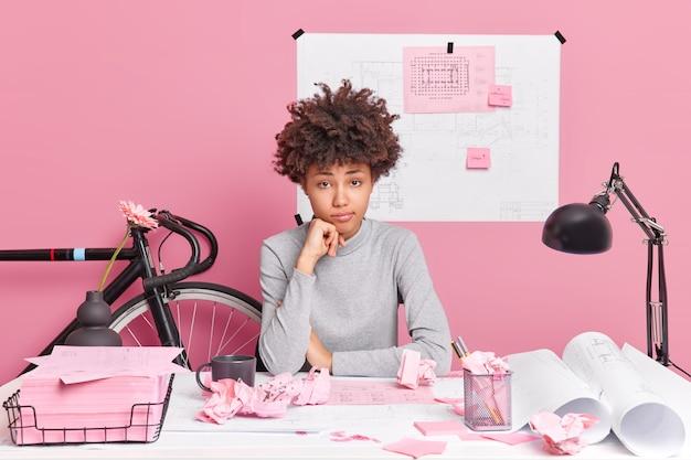 Vermoeide krullende afro-amerikaanse vrouwelijke student werkt aan cursuswerkproject probeert oplossingen te vinden poses in coworking-ruimte tekent schetsen kijkt aandachtig,