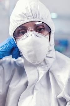 Vermoeide laboratoriumarts met algemeen pak kijkend naar camera in uitgerust laboratorium. overwerkte vrouwelijke wetenschapper in biotechnologisch laboratorium die beschermend pak draagt tijdens wereldwijde epidemie.