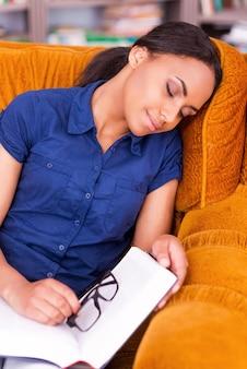 Vermoeide leerling. mooie afrikaanse vrouwelijke student die in een fauteuil slaapt terwijl hij een boek vasthoudt