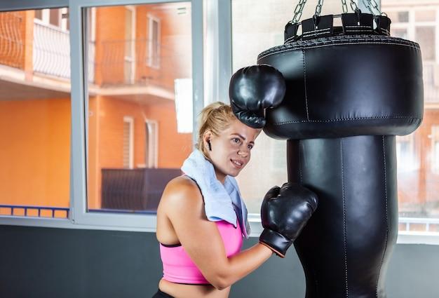 Vermoeide maar lachende blonde bokservrouw die met haar ellebogen op een bokszak rust met een handdoek om haar nek