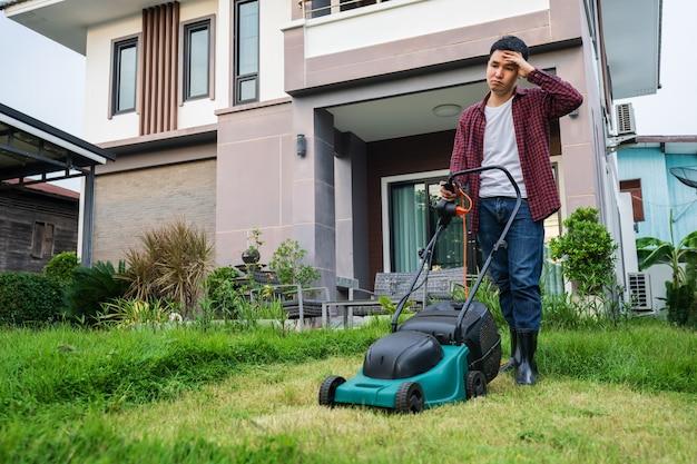 Vermoeide man die een grasmaaier gebruikt om thuis gras te maaien