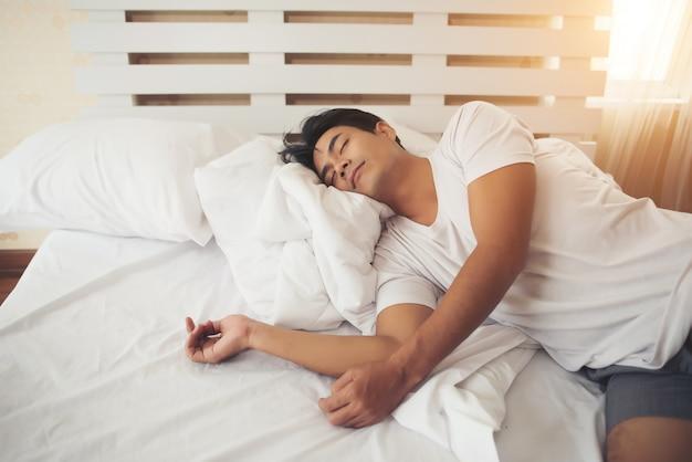 Vermoeide man die slaap aan bed ligt