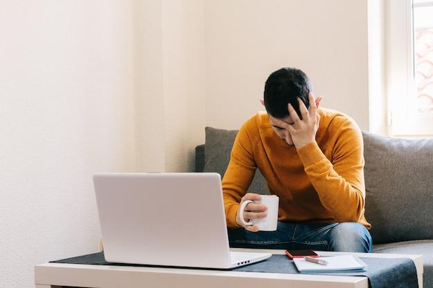 Vermoeide man die thuis werkt met een laptop die zijn gezicht bedekt terwijl hij op de bank in zijn woonkamer zit. vermoeidheid en arbeidsuitbuiting concept