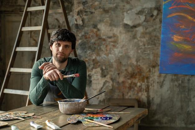 Vermoeide man in een kunststudio zit op een stoel na het schilderen van een abstract schilderij, een moderne en succesvolle kunstenaar houdt een penseel in zijn handen