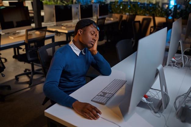 Vermoeide man in glazen werkt op computer, kantoorlevensstijl. mannelijke persoon op desktop, moderne werkplek