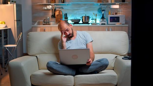 Vermoeide man in pyjam die op internet lifestyle-informatie surft