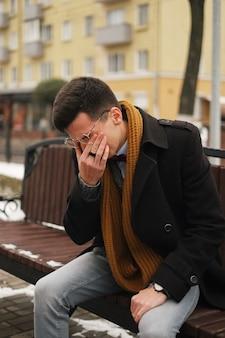 Vermoeide man, jonge hipster, zittend op een bankje, wrijft zijn ogen in het park