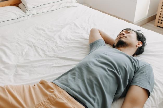 Vermoeide man ligt op het bed terwijl hij geen energie meer heeft