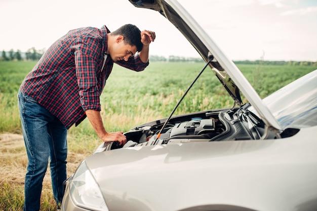 Vermoeide man probeert een kapotte auto te repareren. voertuig met open motorkap langs de weg