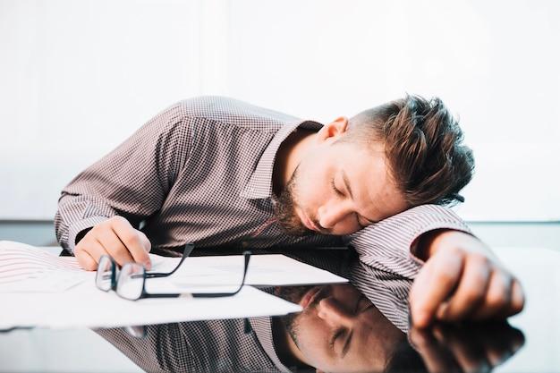 Vermoeide man slapen in kantoor