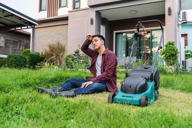 Vermoeide man zit met een grasmaaier om thuis gras te maaien