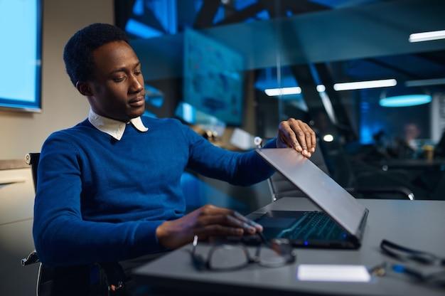 Vermoeide manager die laptop sluit, levensstijl op kantoor. mannelijke persoon aan tafel, donker zakencentrum interieur, moderne werkplek