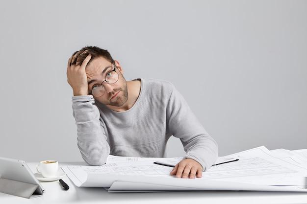 Vermoeide mannelijke illustrator die vermoeidheid is na langdurig tekenen