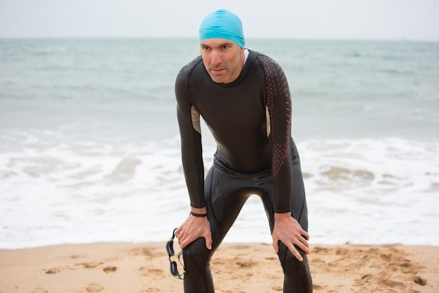 Vermoeide mannelijke zwemmer die zich op strand bevindt