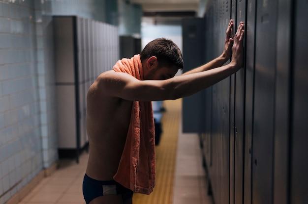 Vermoeide mannelijke zwemmer in kleedkamer