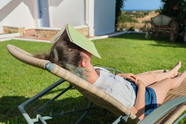Vermoeide meisjesslaap met boek op haar gezicht. tienermeisje liggend op tuin ligstoel op gazon in de buurt van huis, zonnige zomerdag