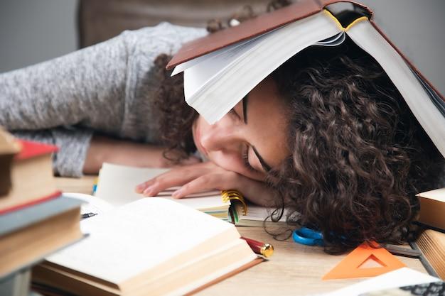Vermoeide meisjesstudentenboeken in hoofd.