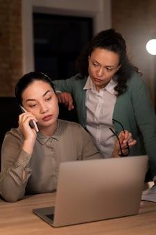 Vermoeide mensen op kantoor die laat aan het werk zijn