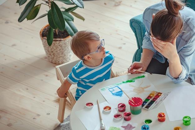 Vermoeide moeder en kind met autisme schilderen samen aquarel op