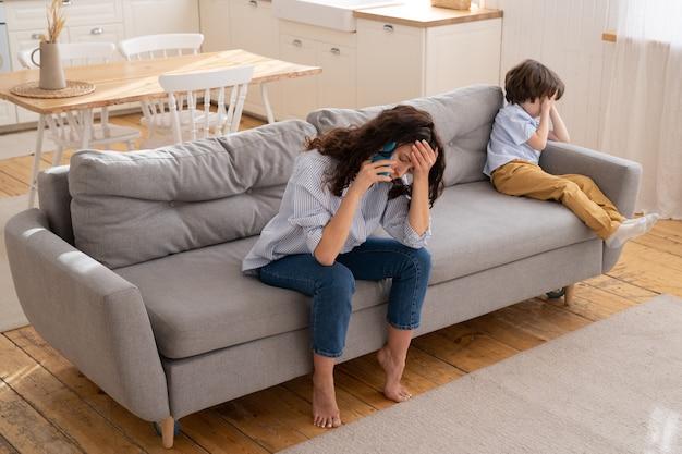 Vermoeide moeder klaagt over het wangedrag van de kleine koppige zoon tijdens het telefoontje naar vader