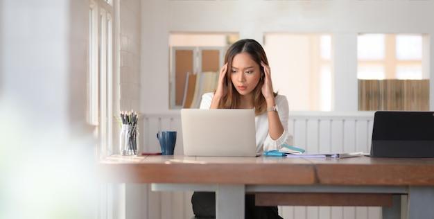 Vermoeide mooie aziatische bedrijfsvrouw die met hoofdpijn in bureauruimte werkt