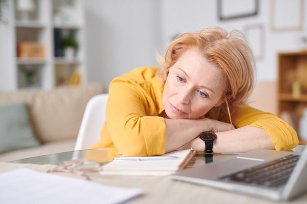 Vermoeide of peinzende rijpe blonde onderneemster die op bureau voor laptop ligt terwijl het hebben van een korte pauze midden op de werkdag