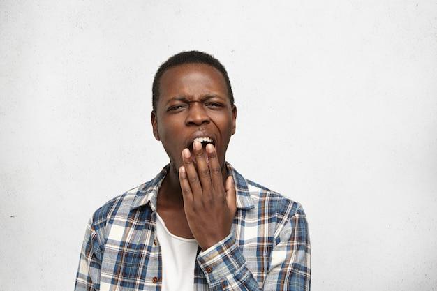 Vermoeide of verveelde afro-amerikaanse jongeman die zijn mond bedekt terwijl hij geeuwt, zich uitgeput voelt na een zware dag op het werk. zwarte mannelijke student die slaperige saaie blik hebben tijdens geschiedenisles op universiteit