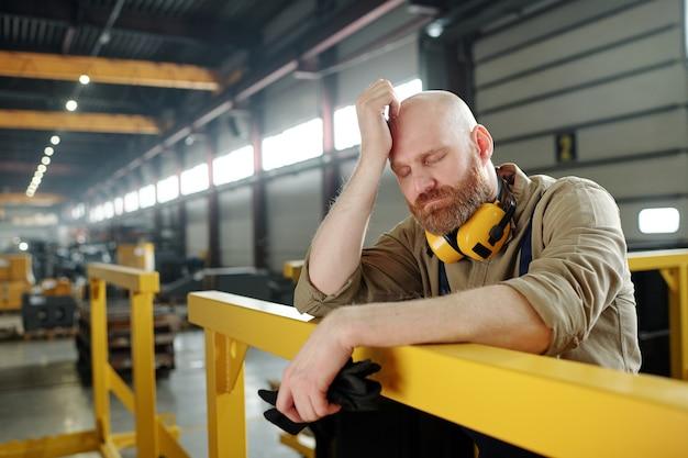 Vermoeide of zieke kale ingenieur die zijn hoofd aanraakt terwijl hij tijdens een pauze in het midden van de werkdag in de werkplaats door de staaf leunt