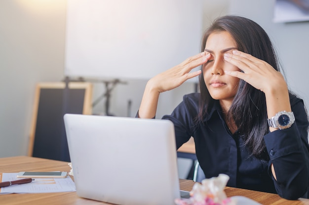 Vermoeide onderneemster met oogpijn tijdens het werken in bureauoverwerken.