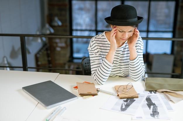 Vermoeide ontwerper in vrijetijdskleding die zich probeert te concentreren terwijl hij per werkplek nieuwe modeschetsen bedenkt