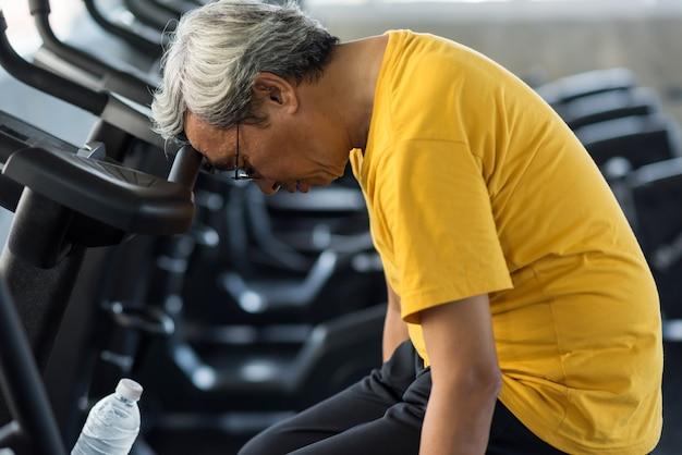 Vermoeide oude man lijdt aan een hartaanval in de sportschool
