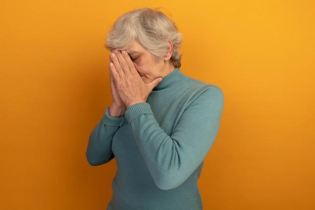 Vermoeide oude vrouw die een blauwe coltrui draagt die in profielweergave staat en de handen bij elkaar houdt op het gezicht met gesloten ogen geïsoleerd op een oranje muur met kopieerruimte