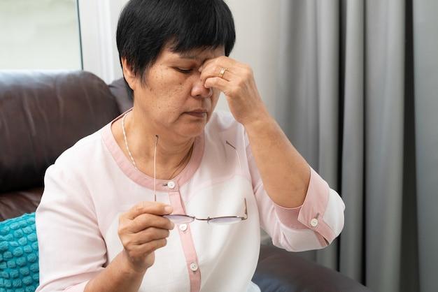 Vermoeide oude vrouw die oogglazen verwijdert, ogen masseert na het lezen van document boek.