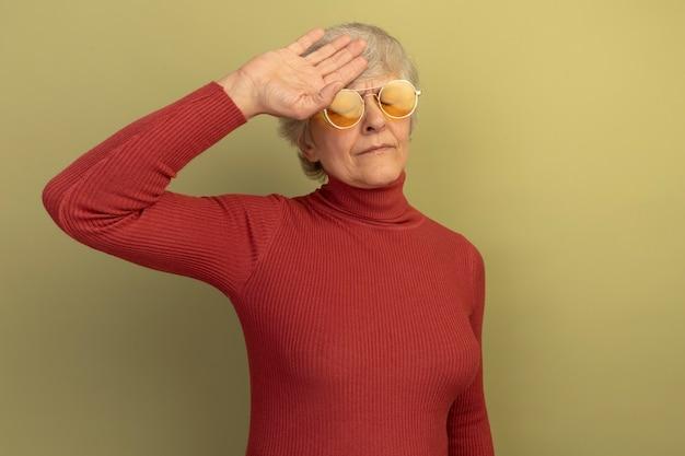 Vermoeide oude vrouw met een rode coltrui en een zonnebril die haar hoofd aanraakt met gesloten ogen