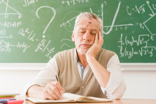 Vermoeide oude wiskundeleraarsslaap bij bureau