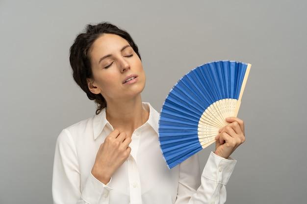 Vermoeide oververhitte vrouwelijke werknemer knoopt de bovenste knoop van de blouse los, met behulp van een golfventilator lijdt aan hitte zweten