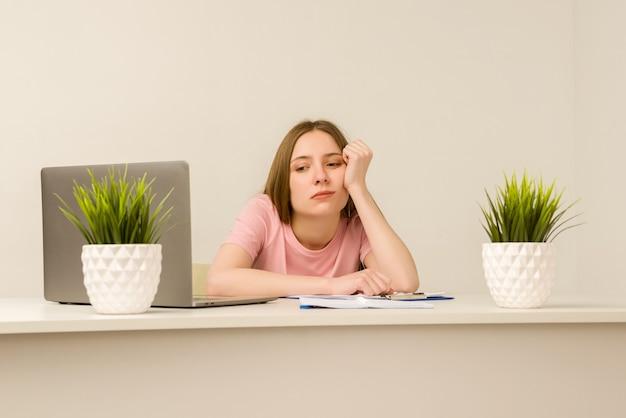 Vermoeide overwerkte jonge stagiaire vrouw die met een laptop in een kantoor werkt